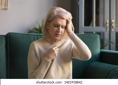 Unhealthy mature woman sitting on couch at home closed eyes touch head feels overheated, aged female having health problems, suffers migraine, high blood pressure, ageing process or menopause concept