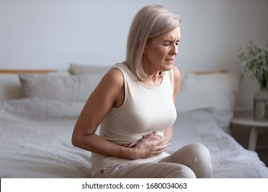 Unhealthy middle aged frowning woman sitting on bed, putting hands on belly, suffering from strong stomach ache. Unhappy older lady having painful feeling in abdomen, pancreatitis gastritis symptom.