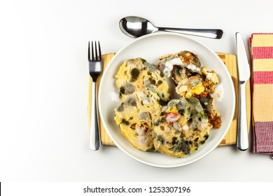 Unhealthy moldy food on a plate. Poisoned food. Dangerous lunch. Bacteria on a plate