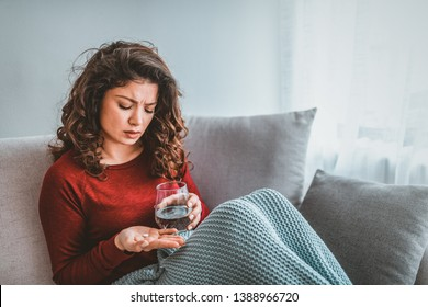 Unhealthy sick woman suffers from insomnia or headache, takes sleeping pill while sitting in bed with glass of water, depressed girl holds antidepressant meds, painkiller for menstrual pain, close up