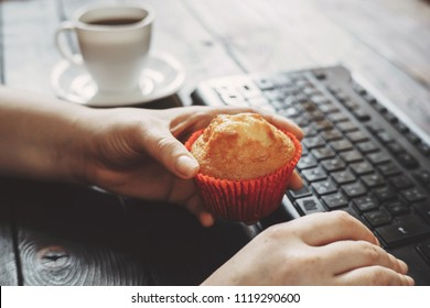 Unhealthy snack, compulsive overeating, mindless snacking, junk food. Woman eating muffin and drinking coffee at workplace.