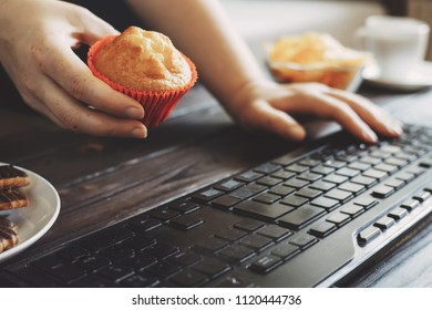 Unhealthy snack, junk food, sweets for lunch. Woman eating muffin at workplace