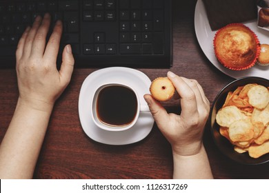 Unhealthy snack at work time. Compulsive indulgence, overeating, stress, high calorie, fattening junk food, weight gain. Woman eating muffin at workplace