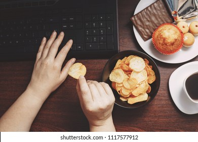 Unhealthy snack at workplace. Hands of woman working at computer and taking chips from the bowl. Bad habits, junk food, high calorie eating, weight gain and lifestyle concept
