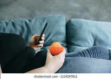 Unhealthy snacking, sedentary lifestyle, compulsive overeating. Obese woman laying on sofa with smartphone eating muffin