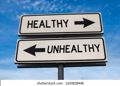 Unhealthy vs healthy. White two street signs with arrow on metal pole with word. Directional road. Crossroads Road Sign, Two Arrow. Blue sky background. Two way road sign with text.