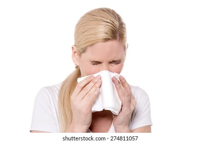 Unhealthy woman blowing  her nose into a tissue
