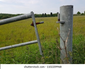 Unhinged - A metal farm gate leading to a crop field detached from the broken hinge at the top of the post