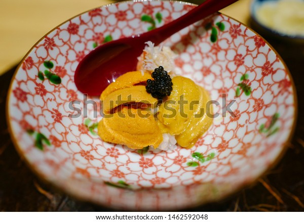 Uni don with 2 types of uni or urchin, Murasaki uni and Bafun uni topped with caviar with alaska crab underneath on japanese style bowl
