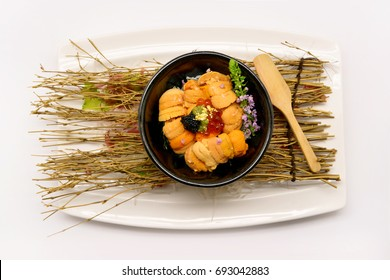 Uni don (Uni on rice) in black bowl on white plate and white background
