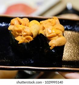 Uni sushi on black dish