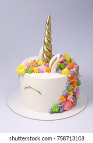 Unicorn baby cake decorated with colored cream, meringues and golden horn