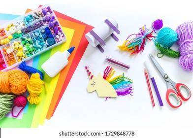 Einhornkarton und Papierhandwerk. Die Hände der Kinder tun das. Wie man ein Kind unterhält. Kindergarten und Schule