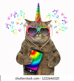 The unicorn cat in headphones is listening to music from a smartphone. White background.