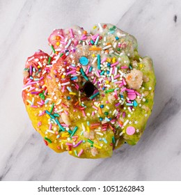 Unicorn donut with colorful glaze and sprinkles on marble surface