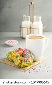 Unicorn donuts with colorful glaze and sprinkles and a cup of coffee
