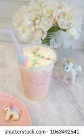 Unicorn drink. Strawberry and caramel milk drink with whipping cream and colorful rainbow starry sugar topping