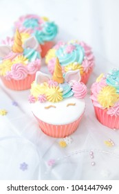 Unicorn fondant cupcakes frosting with butter cream (pastel color) serve with milk.