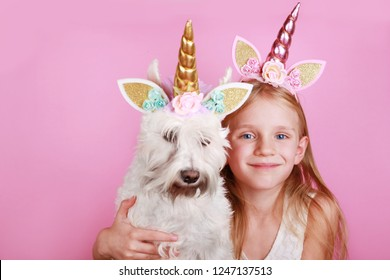 The Unicorn Girl with unicorn dog schnauzer. Young little beautiful blonde girl on pink background, copy space