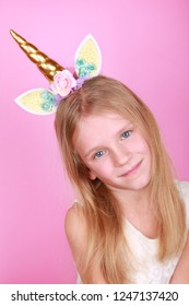 The Unicorn Girl. Young little beautiful blonde girl on pink background, copy space