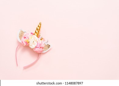 Unicorn headband with flowers and gold horn on blue background.