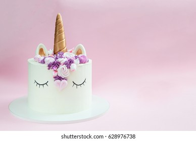 Unicorn layered cake decorated with meringues. Pink background.