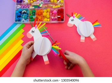 Unicorn made of paper on a pink background. Children's hands make crafts. Magical horse color rainbow. Fulfillment of desires.