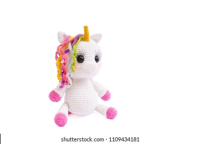 Unicorn plush doll isolated on white background. A crochet doll of a white unicorn. Amigurumi of cute animal.