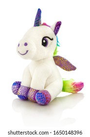 Unicorn plush toy. Isolated on white background with shadow reflection. Unicorn plaything on white reflective underlay. Studio shot. Closeup shot.
