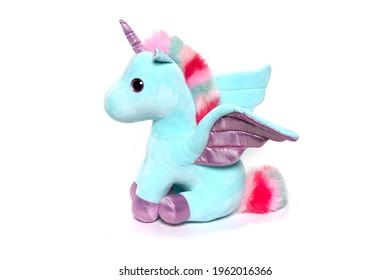 Unicorn plush toy sitting. Isolated on white background