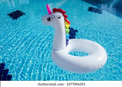 Unicorn pool float in blue water background, inflatable swim tube. Pool party, summer holidays, beach vacation. Fantasy swim ring for summer pool trip. Copyplace, place for text