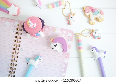 Unicorn stationery. Keeping diary with sweet unicorn pens and pencils with cute macarons and cookie. Little girl's diary. Day dreaming concept