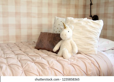 Unicorn stuffed toy leaning against bed cushions in a girls bedroom.