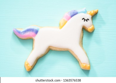 Unicorn sugar cookies decorated with royal icing and food glitter on a blue background.