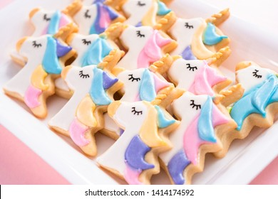 unicorn sugar cookies decorated with royal icing and food glitter on a pink background.