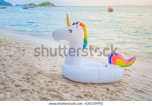 Unicorn swim tube on the beach, Koh Lipe, Satun, Thailand Inflatable unicorn. Fantasy Swim Ring for Summer Pool Trip Beautiful white sand beach and sea.