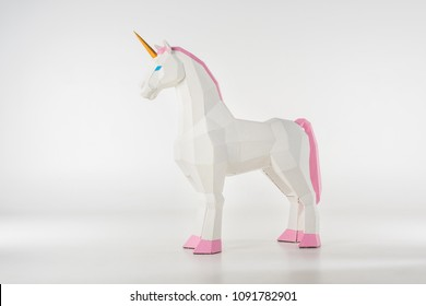 unicorn toy with golden horn with pink hooves on white