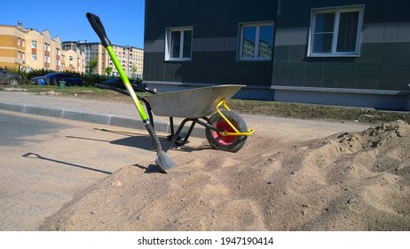 Unicycle wheelbarrow with one wheel, shovel, pile of sand near residential building. City street. Construction site. Road works. Restoration and reconstruction concept. Rebuilding. Civil engineering.