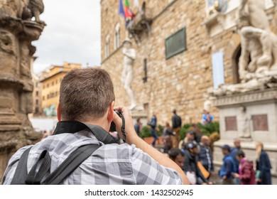 A unidentfied photographer outside the Palazzo Vecchio taking a photo of a statue of David replica.