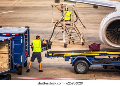 Unidentifiable airport worker loads baggages into an airplaine