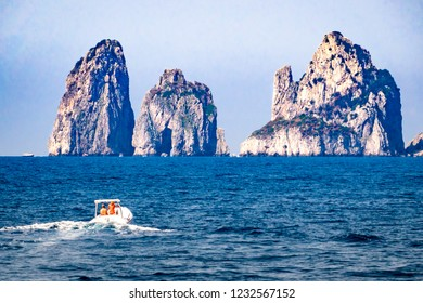 """Unidentifiable boaters  approach the three rocky """"stacks"""" off the island of Capri in Italy, known as  I Faraglioni."""