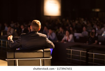 Unidentifiable Businessman on Stage Wearing a Suit with Hand Up Presenting to Blurred Audience at Conference Hall Tech Presentation. Technology Manager Education Lecture
