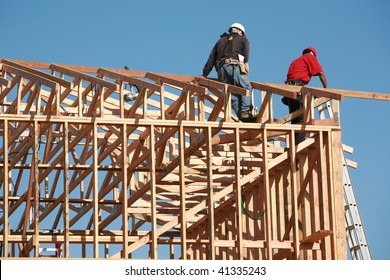 unidentifiable construction workers work on framing a building