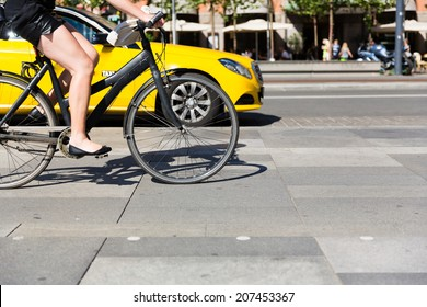 Unidentifiable female person riding a bicycle in the city centre.