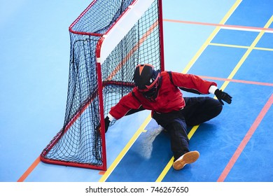 Unidentifiable floorball goalkeeper. Children playing floorball