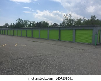 Unidentifiable green storage units in a rural setting. The storage units have green doors.