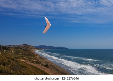 Unidentifiable hang glider flying above ground and ocean on a white wing at Fort Funston in San Francisco, one of the premier hang-gliding spots in the country
