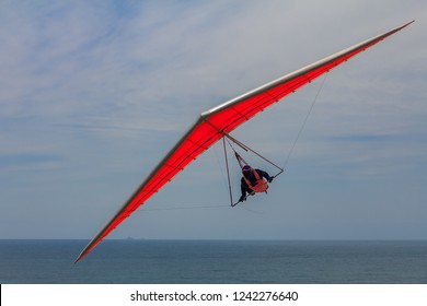 Unidentifiable hang glider flying on an orange wing at Fort Funston in San Francisco, one of the premier hang-gliding spots in the country
