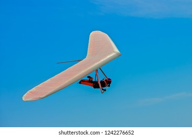 Unidentifiable hang glider flying on a white wing at Fort Funston in San Francisco, one of the premier hang-gliding spots in the country