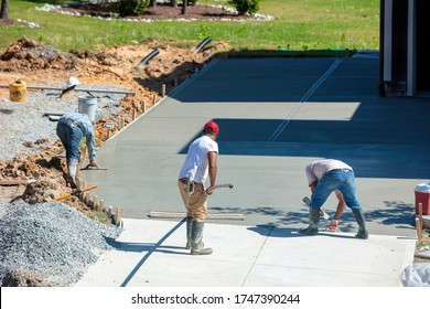 Unidentifiable hispanic men working on a new concrete driveway at a residential home